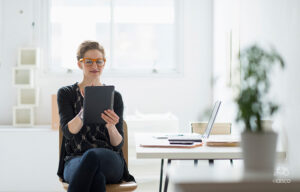 Woman sitting at her desk on an ipad