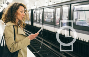 Woman on her phone waiting for the subway