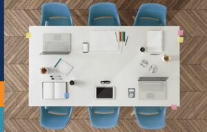 Overhead shot of a table with devices and office supplies.